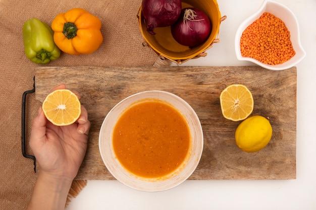 白い表面に分離されたカラフルな唐辛子と袋布の上の木製のキッチンボードのボウルにレンズ豆のスープと新鮮なレモンを持っている女性の手の上面図