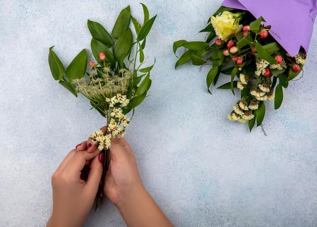 白で隔離される花の花束と果実の葉を持っている女性の手の上から見る