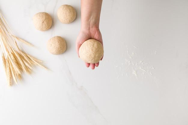 텍스트에 대 한 공간을 가진 세 성형 빵 반죽, 밀, 밀가루와 대리석 테이블에 성형 빵 반죽을 들고 여성 손의 상위 뷰