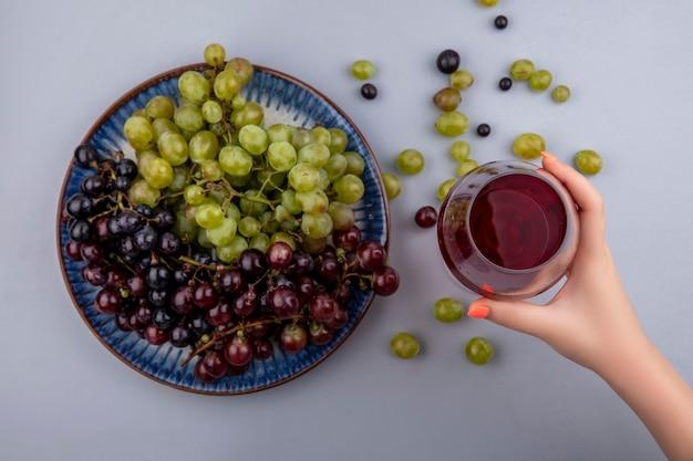 Вид сверху женской руки, держащей красное вино в рюмке и виноград в тарелке и на сером фоне