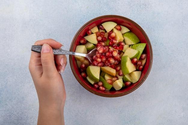 白地に赤いボウルにザクロの種子とみじん切りりんごのスプーンを持っている女性の手の上から見る
