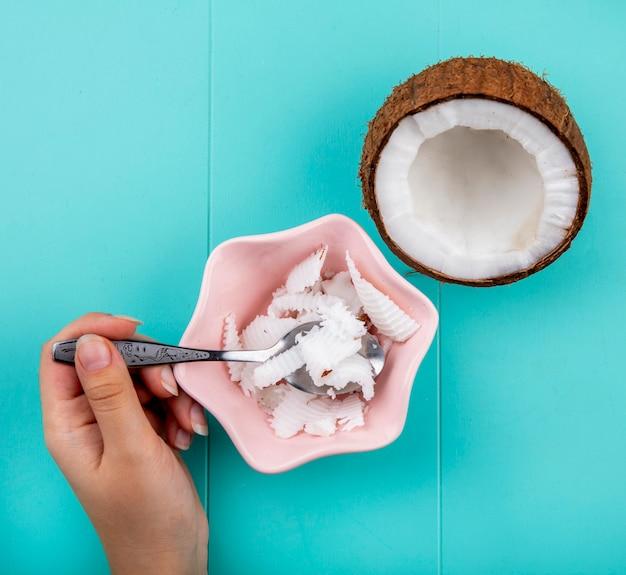青に半分にされたココナッツとピンクのボウルにココナッツの果肉とスプーンを持っている女性の手の上から見る