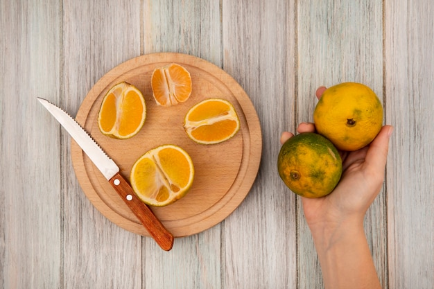 灰色の木の表面にナイフで木製のキッチンボードに分離された半分のみかんとタンジェリンを持っている女性の手の上面図