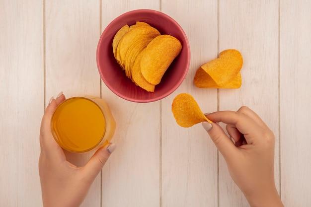 ベージュの木製テーブルにオレンジジュースのガラスとおいしいクリスピーチップスを持っている女性の手の上面図