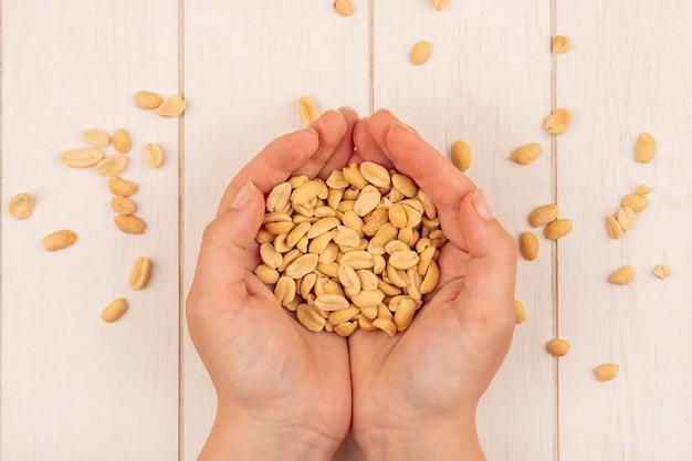 Вид сверху женской руки, держащей вкусные соленые кедровые орехи на бежевом деревянном столе