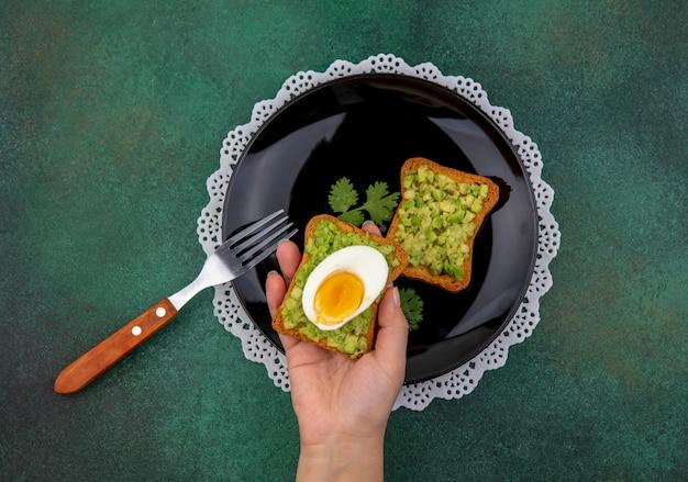 Вид сверху женской руки, держащей тостовый хлеб с мякотью авокадо и яйцом на миске с вилкой на зеленом