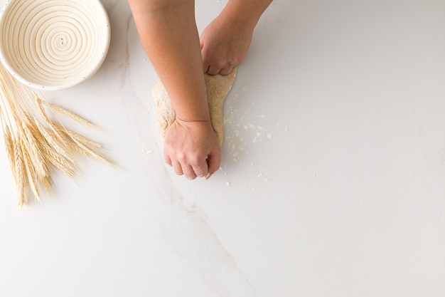 빈 빵 그릇과 텍스트에 대 한 공간을 가진 밀 대리석 테이블에 빵 반죽을 반죽하는 여성 손의 상위 뷰