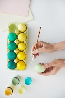 白い背景、コピースペースにパステルグリーンと黄色のイースターエッグを描く女性の手の上面図