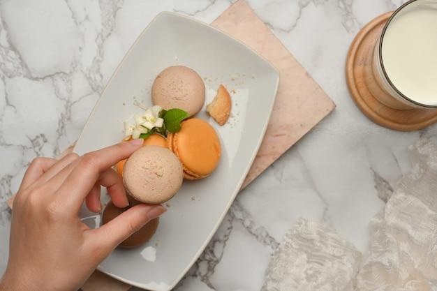 大理石のテーブルの上のミルクと一緒に食べるためにマカロンを選ぶ女性の手の上面図