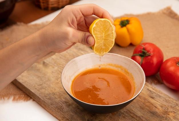 カラフルなピーマンとトマトが木の表面に分離された袋布の上の木製のキッチンボード上のボウルに新鮮なレモンをスープに絞る女性の手の上面図