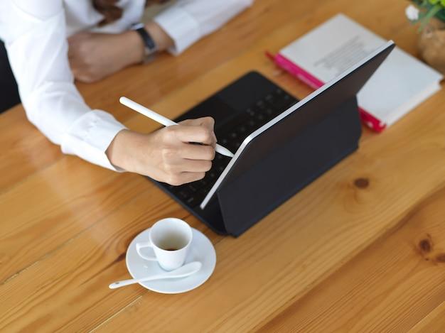 Вид сверху женской руки с помощью цифрового планшета на деревянном столе с кофейной чашкой и документами