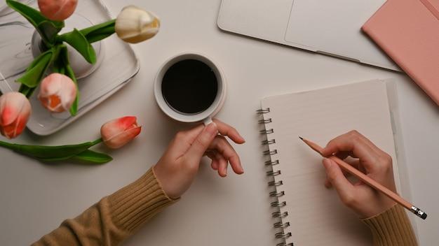 空白のノートに書き込み、ホームオフィスの机にコーヒーマグを保持している女性の上面図