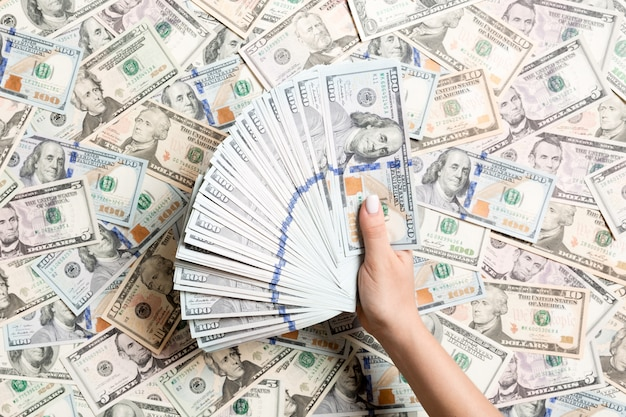 別のドルの背景にお金を数える女性の手の平面図です。借金。投資コンセプト