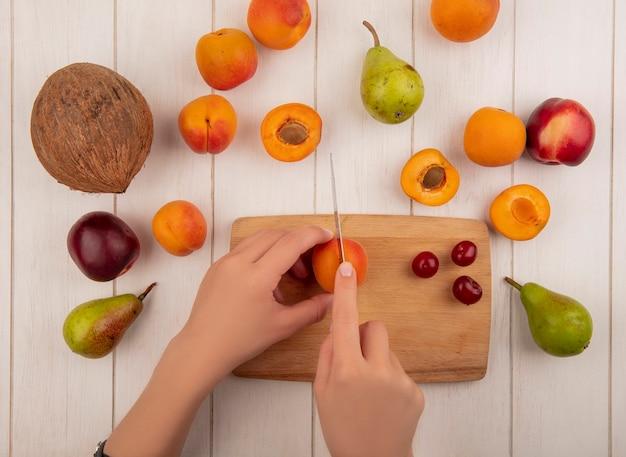 Вид сверху женских рук, режущих абрикос ножом и вишнями на разделочной доске с рисунком из груш, персиков, абрикосов и кокоса на деревянном фоне