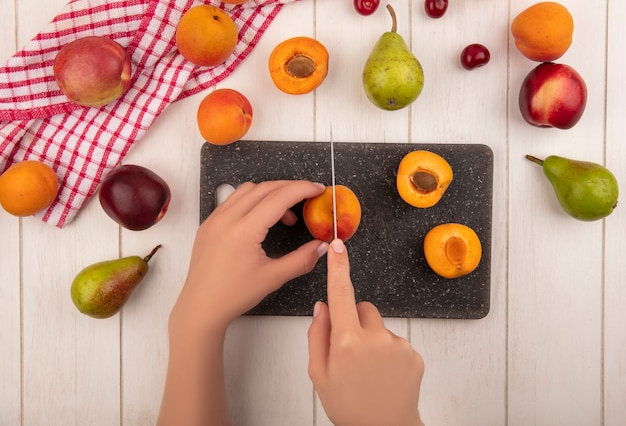 Вид сверху женских рук, режущих абрикос ножом и половину нарезанного абрикоса на разделочной доске с рисунком груш, персиков, абрикосов и вишен на клетчатой ткани и на деревянном фоне