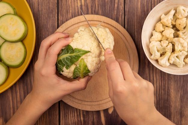 木製の表面のボウルにカリフラワーのつぼみとナイフで木製のキッチンボードでカリフラワーを切る女性の手の上面図