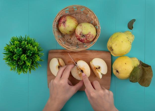 青い背景の上のナイフで木製のキッチンボードで新鮮なリンゴを切る女性の手の上面図