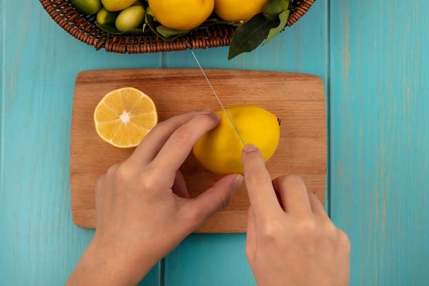 青い木の表面のバケツにキンカンやレモンなどの果物とナイフで木製のキッチンボードで新鮮なレモンを切る女性の手の上面図