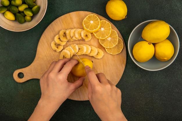 緑の表面のボウルにkinkansとナイフで木製のキッチンボードで新鮮なレモンを切る女性の手の上面図