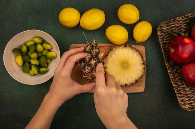 緑の背景に分離されたレモンとボウルにkinkansとナイフで木製のキッチンボードで新鮮なパイナップルを切る女性の手の上面図