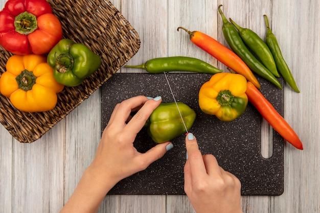 灰色の木製の壁に分離された唐辛子とナイフで黒いキッチンボードに緑のピーマンを切る女性の手の上面図