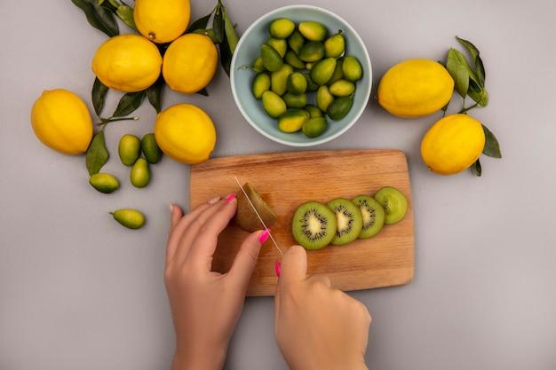 白い背景で隔離のレモンとボウルにkinkansとナイフで木製のキッチンボードでキウイを切る女性の手の上面図