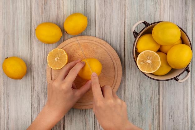 灰色の木製の表面に分離されたレモンとボウルにレモンとレモンとナイフで木製のキッチンボードでレモンを切る女性の手の上面図