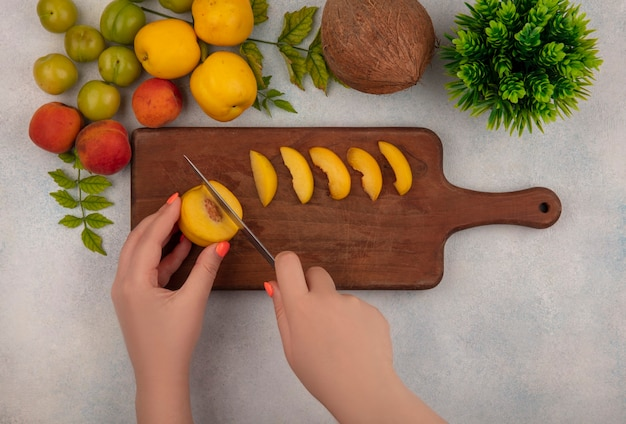 Вид сверху на женские руки, режущие персик на деревянной кухонной доске с зелеными алычами на белом фоне