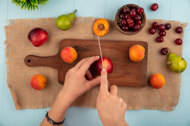 Вид сверху на женские руки, режущие персик ножом и абрикосы на разделочной доске и вишни в миске персик груша абрикос на мешковине и синем фоне