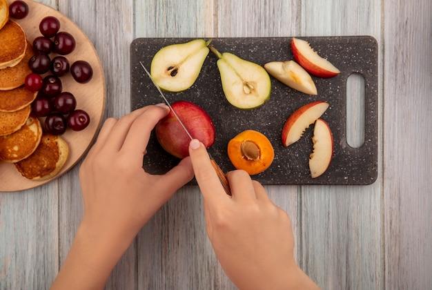 Вид сверху на женские руки, режущие персик ножом и нарезанный персик, разрезанный грушевый абрикос на разделочной доске и блины с вишней на разделочной доске и деревянном фоне