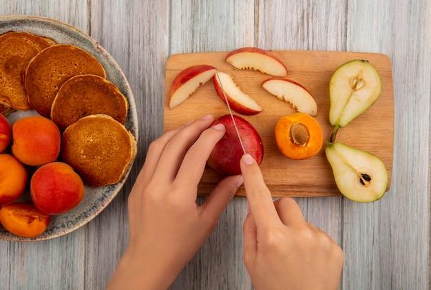 Вид сверху на женские руки, режущие персик ножом и нарезанную персиком грушу на разделочной доске и тарелку блинов с абрикосами на деревянном фоне