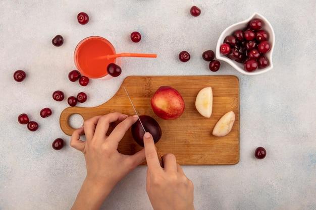 Вид сверху на женские руки, режущие персик ножом на разделочной доске и вишневый сок с миской вишни на белом фоне