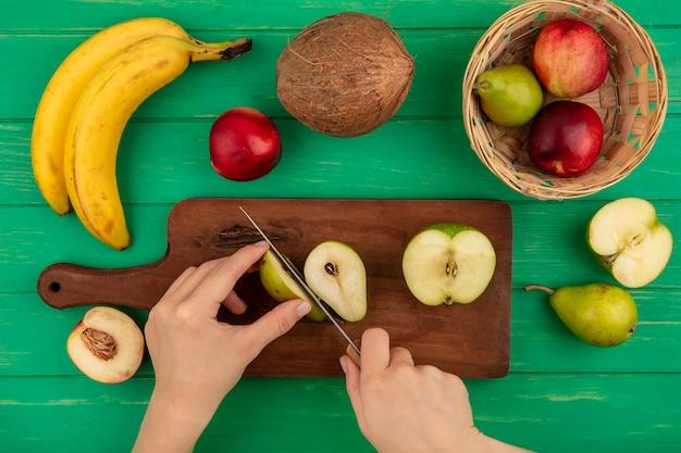 Вид сверху женских рук, режущих грушу ножом и половиной яблока на разделочной доске с персиком, бананом и кокосом на зеленом фоне