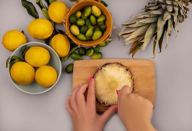 白い表面のバケツにキンカンとボウルにレモンとレモンとナイフで木製のキッチンボードにパイナップルを切る女性の手の上面図