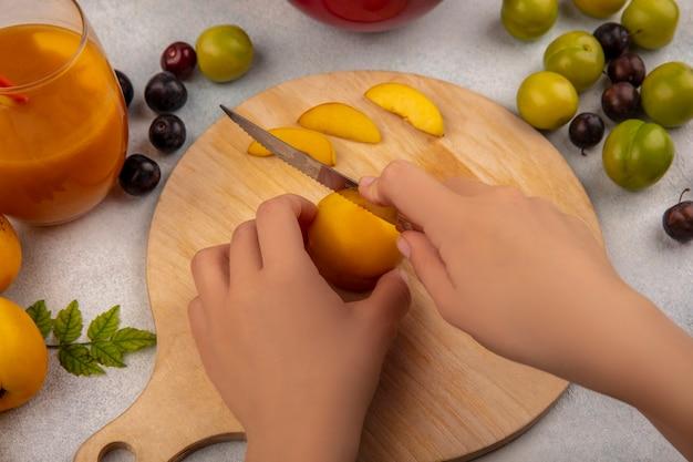Вид сверху женских рук, режущих желтый персик на деревянной кухонной доске ножом с персиками с зелеными алычами, изолированными на белом фоне