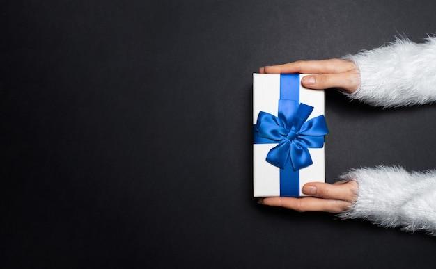 복사 공간 블랙 색상의 질감에 흰색 스웨터를 입고 블루 리본 활과 선물 상자를주는 여성 손의 상위 뷰.