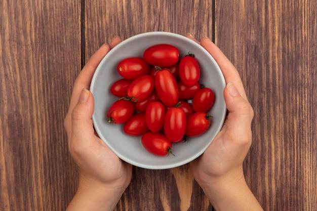 木製の表面に新鮮なトマトのボウルを保持している女性の手の上面図