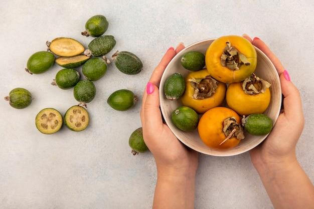 灰色の表面に柿と緑の熟したフェイジョアのボウルを保持している女性の手の上面図