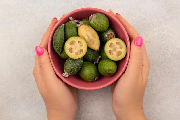 灰色の表面に健康的な緑の熟したフェイジョアのボウルを保持している女性の手の上面図