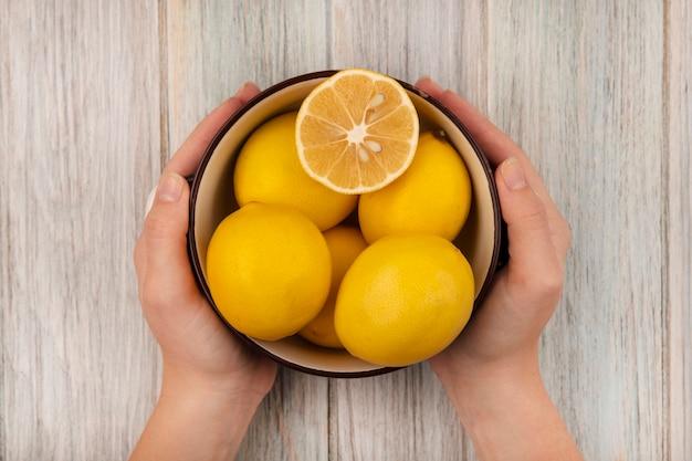 灰色の木の表面に健康なレモンのボウルを保持している女性の手の上面図