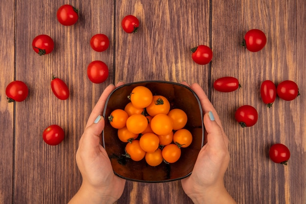 オレンジ色のチェリートマトのボウルを木の表面に保持している女性の手の上面図