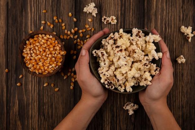 Вид сверху на женские руки, держащие миску попкорна с зернами кукурузы на деревянной миске на деревянном столе
