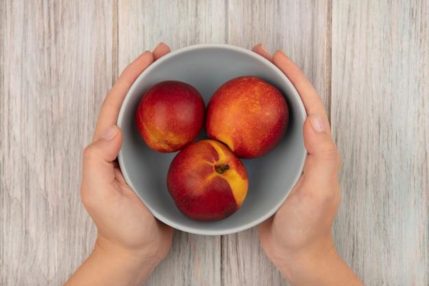 灰色の木の表面に甘い新鮮な桃のボウルを保持している女性の手の上面図