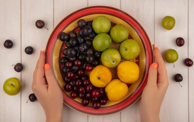 白い木製の背景にグリーンチェリープラムレッドチェリースウィートピーチなどの新鮮な果物をボウルに保持している女性の手の上から見る