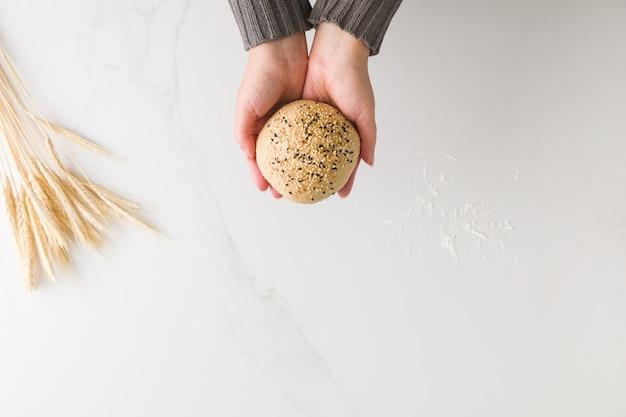 텍스트에 대 한 공간을 가진 밀과 밀가루와 대리석 테이블에 빵을 들고 여성 손의 상위 뷰