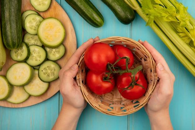 Вид сверху женских рук, держащих ведро свежих помидоров с нарезанными огурцами и цуккини на деревянной кухонной доске с сельдереем, изолированным на синей деревянной стене