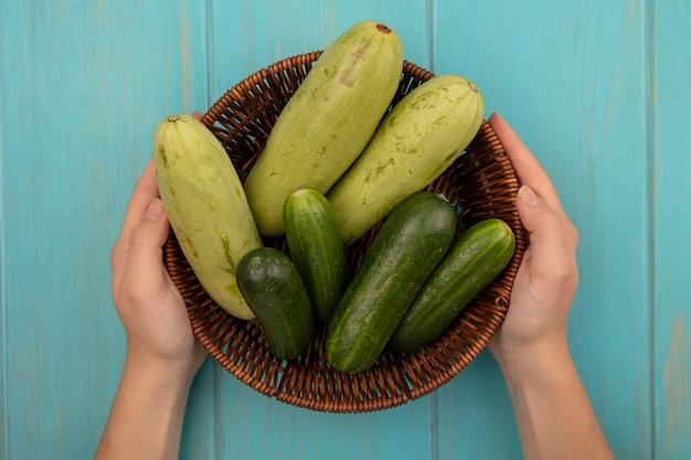 青い木の表面にきゅうりやズッキーニなどの新鮮な野菜のバケツを保持している女性の手の上面図