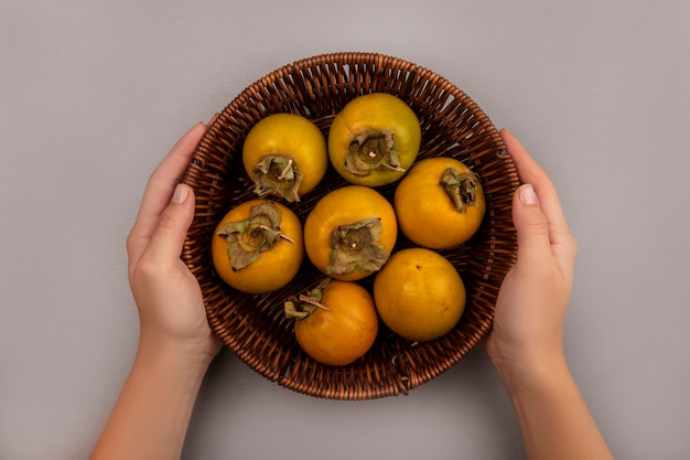 Вид сверху на женские руки, держащие ведро с фруктами хурмы