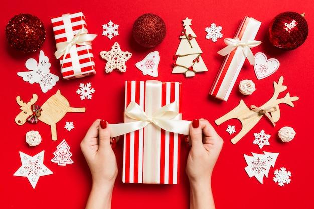 お祝いのクリスマスプレゼントを保持している女性の手の平面図です。休日の装飾。新年の休日の概念