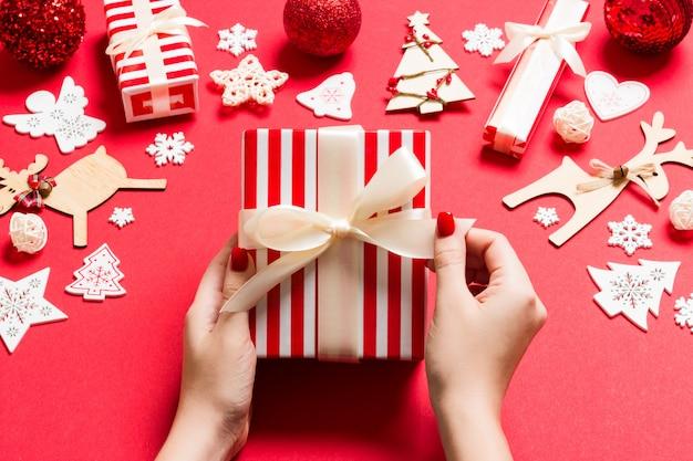 Взгляд сверху женских рук держа рождественский подарок на праздничной красной предпосылке
